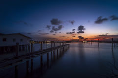 Twilight time on the Songkhla lake, Thailand. Twilight time on the lake with house and wood bridge Stock Photos