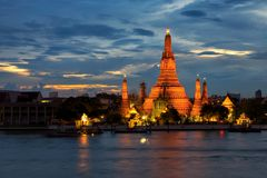 Twilight time of Wat Arun across Chao Phraya River in Bangkok, T. Twilight time of Wat Arun across Chao Phraya River during sunset in Bangkok, Thailand Royalty Free Stock Images