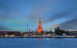 Twilight time of Wat Arun across Chao Phraya River during sunset in Bangkok, Thailand Stock Photo