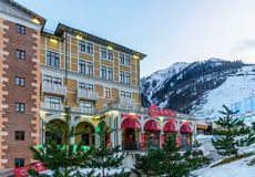Twilight townscape of Gorky Gorod mountain ski resort. Gorky 960 restaurant entrance view with neon exterior sign at winter on sno. Sochi, Russia - January 6 stock photo