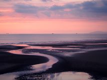 Twilight view of a dark beach with a pink sky after sunset with blue clouds reflected in the water at low tide and a calm sea in. Blackpool lancashire stock photography