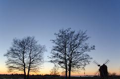 Twilight view with trees and a windmill Stock Image