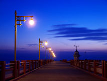 The twilight. The walkway on the bridge extends to the lighthouse in twilight Stock Image