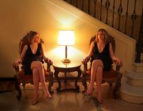 Twin. Sisters sitting on armchair in a luxury interior stock photos