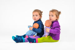 Twin Babies with Dolls Stock Photography