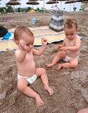 Twin babies playing in the sun-beach time