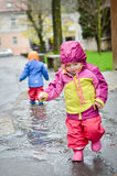Twin babies in rain clothes Stock Images