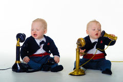 Twin baby boys communicate with old fashioned phones Royalty Free Stock Image