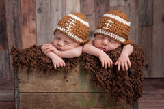 Twin Baby Boys Wearing Football Shaped Hats. Four week old fraternal, twin, newborn baby boys sleeping in a vintage, wooden crate and wearing football shaped royalty free stock photo