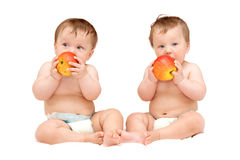 Twin baby girls are eating Royalty Free Stock Image
