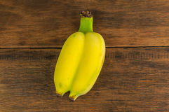 Twin bananas on wood background. Stock Images