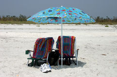 Twin beach chairs. Identical beach chairs and umbrella Royalty Free Stock Photography