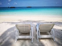 Twin beach chairs on fine white sand royalty free stock photo