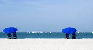 Twin beach umbrellas. Pair of beach umbrellas and chairs to watch sailboats go by in a race Royalty Free Stock Images