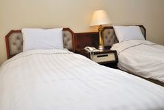 Twin beds in hotel with table lamp lighted Royalty Free Stock Image