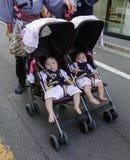 Twin behandla som ett barn i sittvagnen arkivfoton