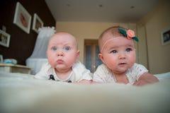 Twin behandla som ett barn pojke- och flickalögn på sängen Arkivbilder