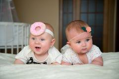 Twin behandla som ett barn pojke- och flickalögn på sängen Royaltyfri Foto