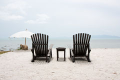 Twin black chair. On white sand beach Stock Image