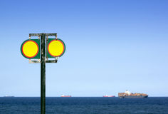 Twin Blank Yellow and Red Cautionary Signs. At entrance to beach with ships in the ocean background royalty free stock image
