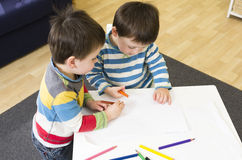 Twin boys drawing at a table together. Twin boys drawing with pencils at a table Royalty Free Stock Images