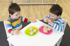 Twin boys eating sandiwches. Twin boys sitting at a table eating sandwiches Royalty Free Stock Photography