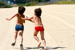 Twin boys play tag at the beach. Twin boys runs after each others playing tag at the beach Royalty Free Stock Image