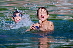 Twin boys play in the water. Twin multi etnjic japanese italian twin boys play in the water Royalty Free Stock Photos