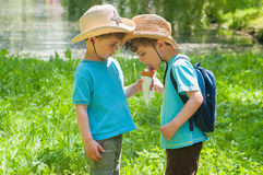 Twin boys share ice cream. Three year old identical twin boys in cowboy hats share ice cream in the park Stock Photos