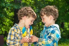 Twin boys share a lollipop. Three year old identical twin boys are holding the candy in the colors of the Ukrainian flag. Candy shows the Ukrainian Trident Stock Photography