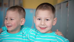 Twin boys smile in the camera. HD stock video footage