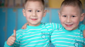 Twin boys smile in the camera. Looking twins boys in camera HD stock footage
