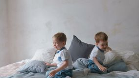 Twin boys toddlers are lying on the bed, throwing pillows, jumping and laughing. Twin boys toddlers are lying on the bed, throwing pillows, jumping and laughing stock video