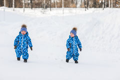 Twin boys walking in the Park in the winter in matching jumpsuits Stock Images
