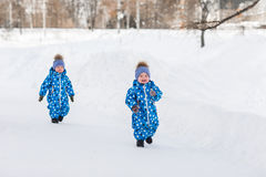 Twin boys walking in the Park in the winter in matching jumpsuits Stock Photo