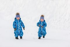 Twin boys walking in the Park in the winter in matching jumpsuits Stock Photography
