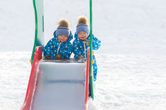 Twin boys walking in the Park in the winter and roll with iron armor royalty free stock photo