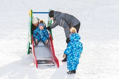 Twin brother rolls down hill, happy family winter walks in the Park royalty free stock photo