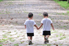Twin brothers. Holding hands along the path stock photo