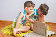 Twin brothers with book Stock Images