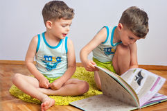Twin brothers with book. Three year old identical twin boys sit on the floor with encyclopedia about animals Stock Photography