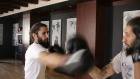 The twin brothers in boxing gloves sparring in the training hall. Chinese martial arts. Wushu. Wudan stock footage