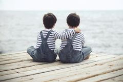 Twin brothers. Brothers sitting at waterfront.Back view Stock Photography