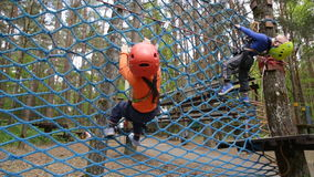 Twin brothers climbing in adventure park. Is a place which can contain a wide variety of elements, such as rope climbing exercises, obstacle courses and zip stock video footage