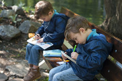 Twin brothers draw with pens in notebooks. Four year old identical twin boys seat on the bench in the park. They are dressed in anoraks and jeans. They draw with Stock Images