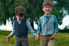 Twin brothers dressed in shirts and vests. Three year old identical twins are in a meadow with a large tree. They are dressed in shirts with vests of different Stock Photos