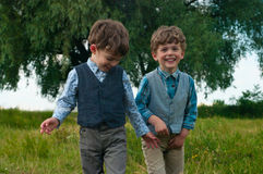 Twin brothers dressed in shirts and vests. Three year old identical twins are in a meadow with a large tree. They are dressed in shirts with vests of different Stock Photo