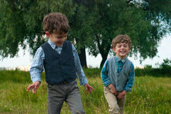Twin brothers dressed in shirts and vests. Three year old identical twins are in a meadow with a large tree. They are dressed in shirts with vests of different Stock Photography