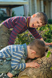 Twin brothers explore the hole. Three year old identical twin boys explore the hole in the vase Royalty Free Stock Photography