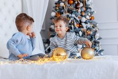 Twin brothers in front of the christmas tree with candles and gifts. love, happiness and big family concept. Twin brothers in front of the christmas tree with royalty free stock photography